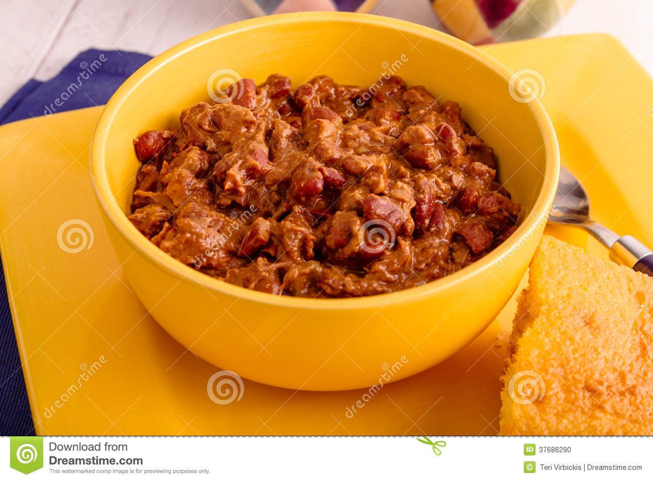 Chili With Red Kidney Beans In Yellow Bowl With Cornbread On Plate