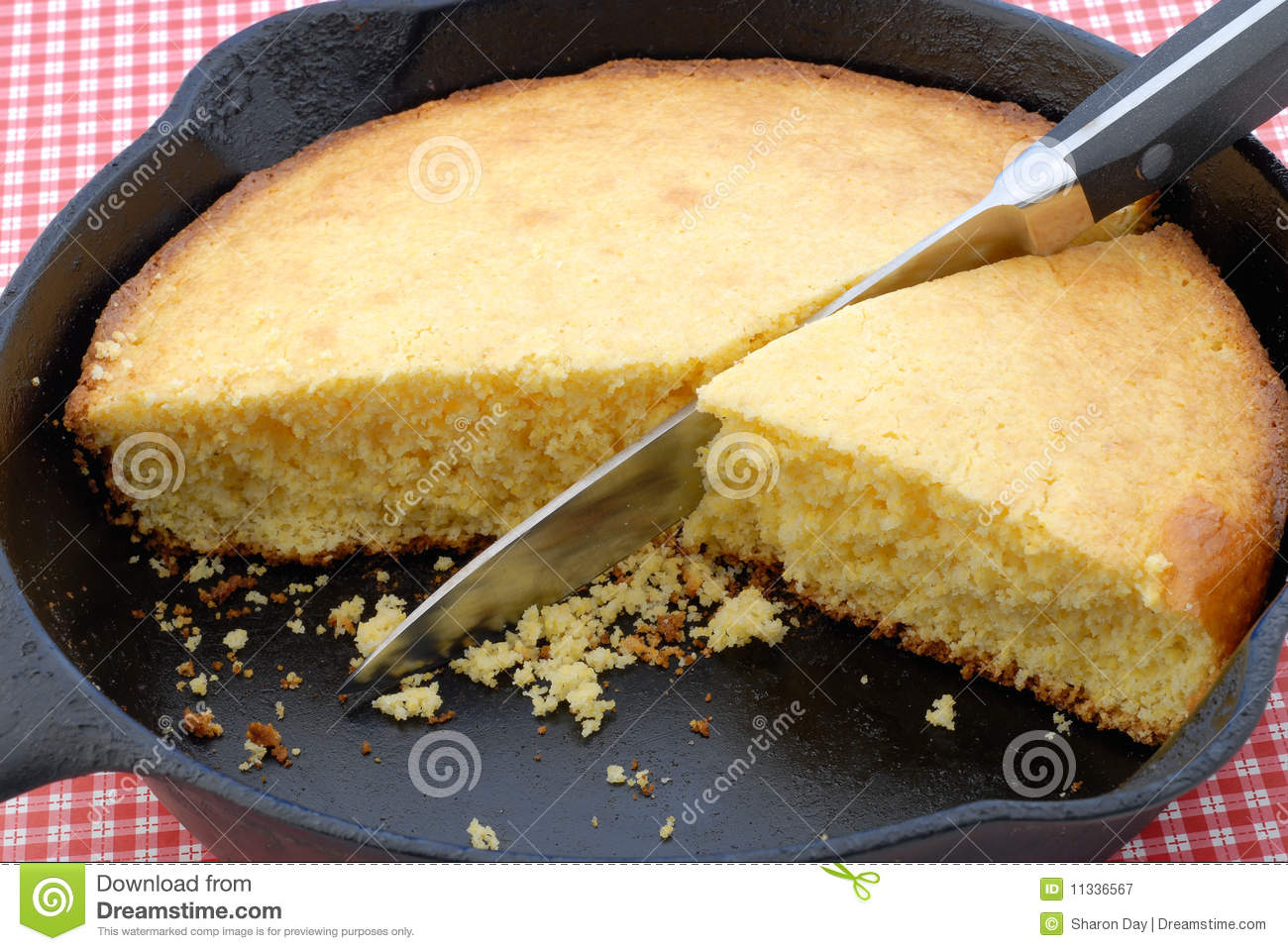 Closeup Of Cornbread In A Cast Iron Skillet Against A Red Checked