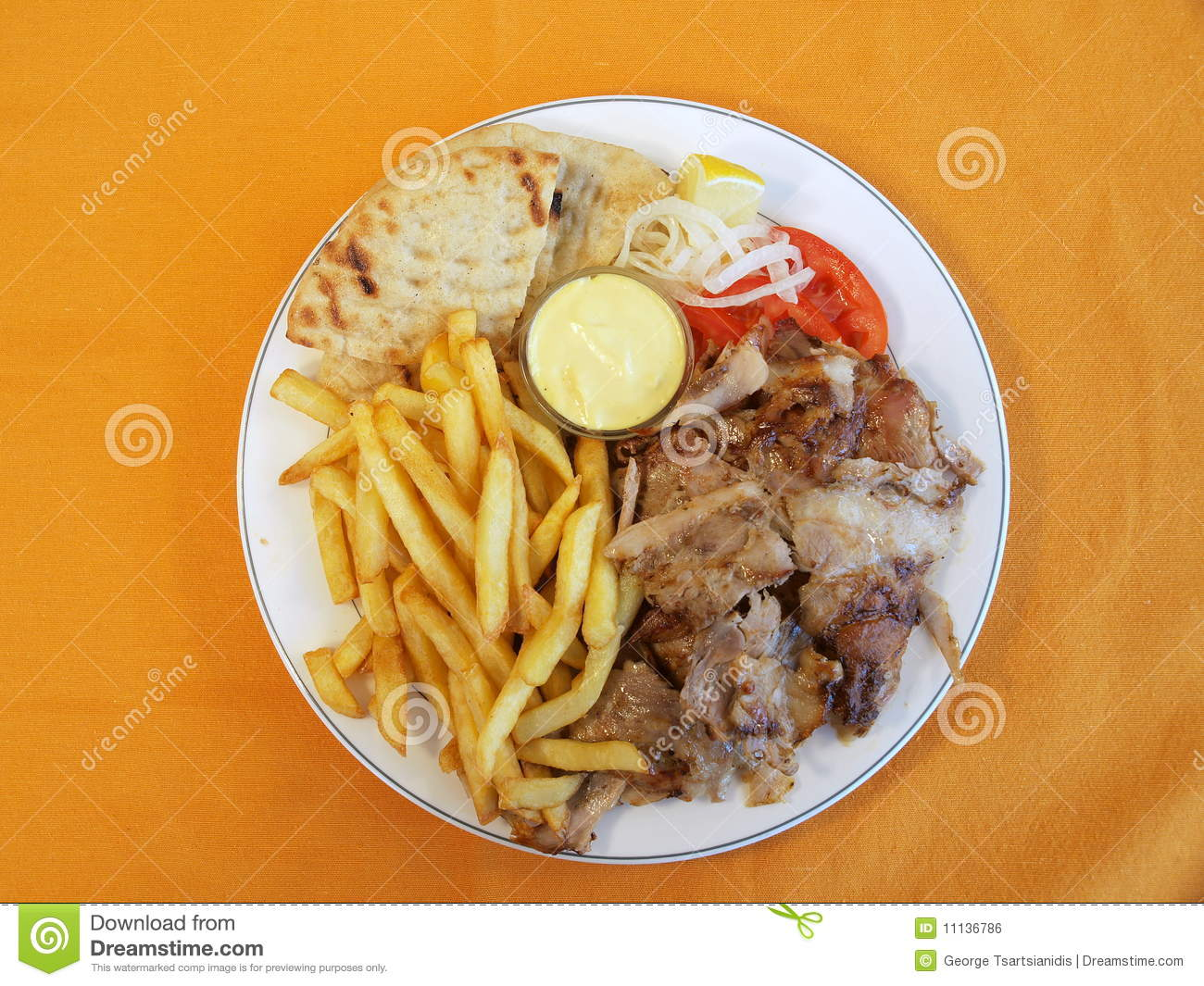 Looking Down On Plate Of Traditional Greek Gyros With French Fries On