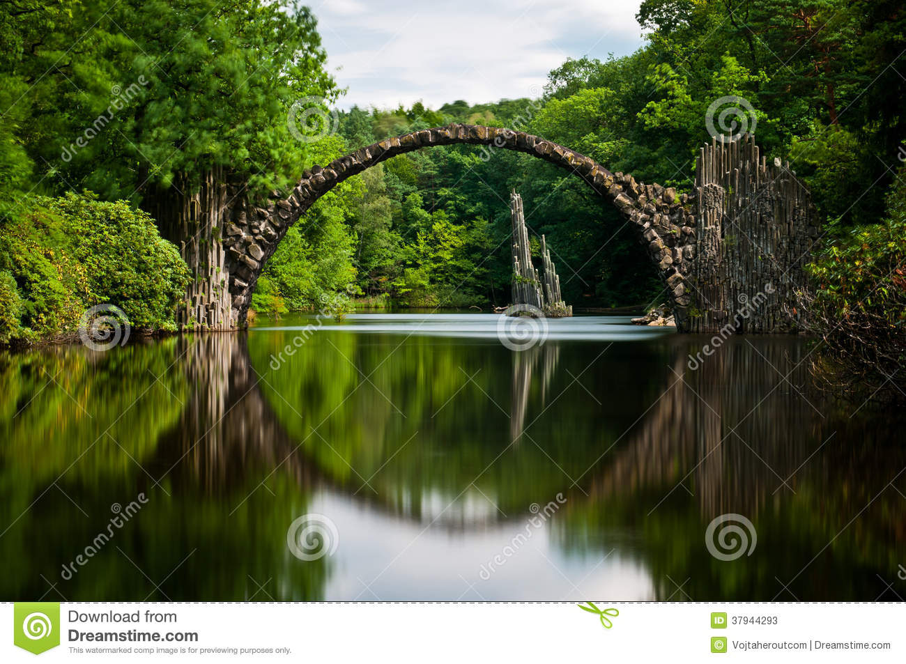 Old Stone Bridge Over The Quiet Lake With Its Reflection In The Water