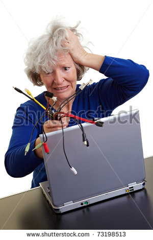 Frustrated Old Woman With Laptop And Many Different Computer Cables