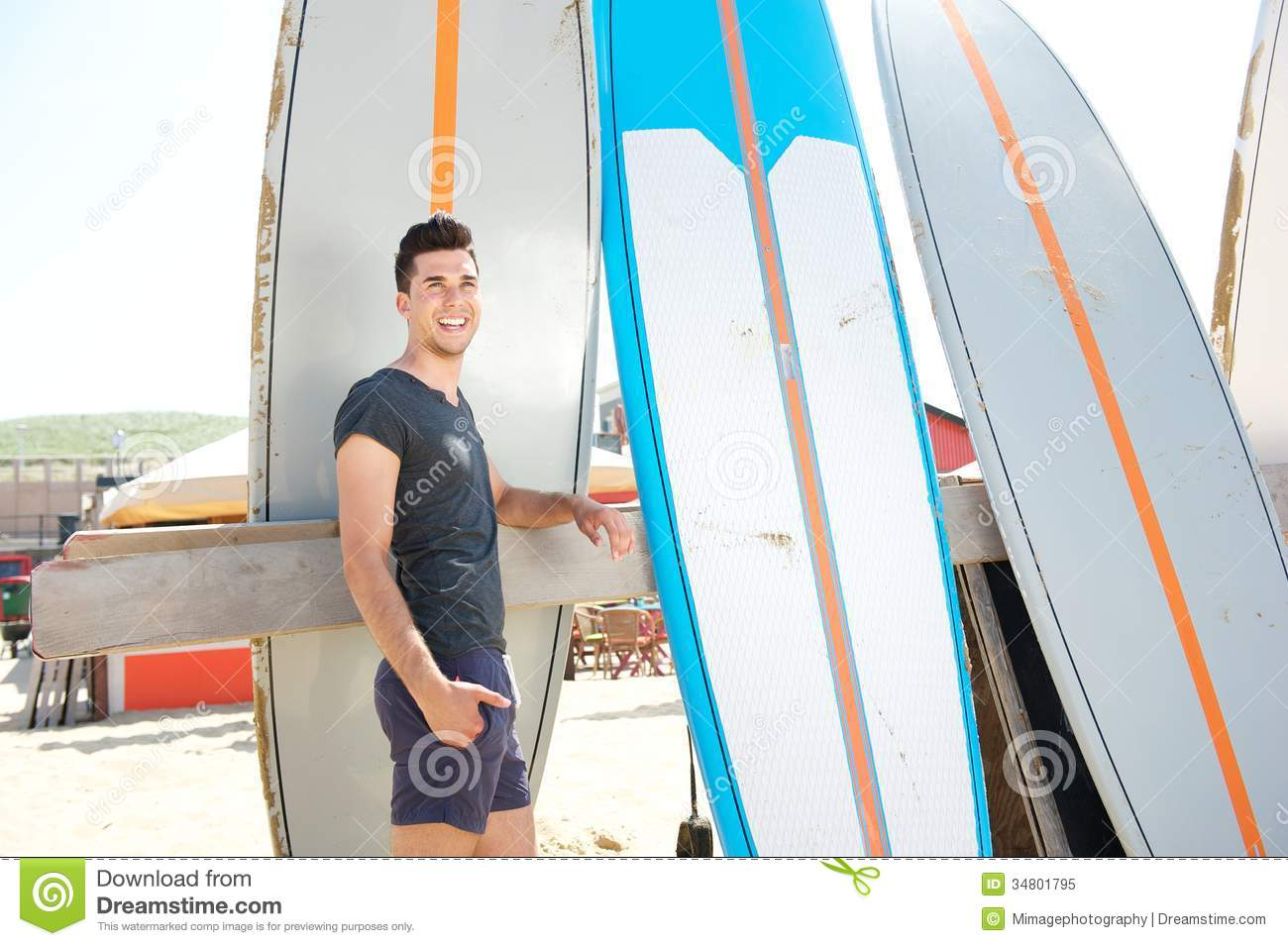 Stock Photo  Portrait Of A Happy Man Standing At Beach With Surfboard