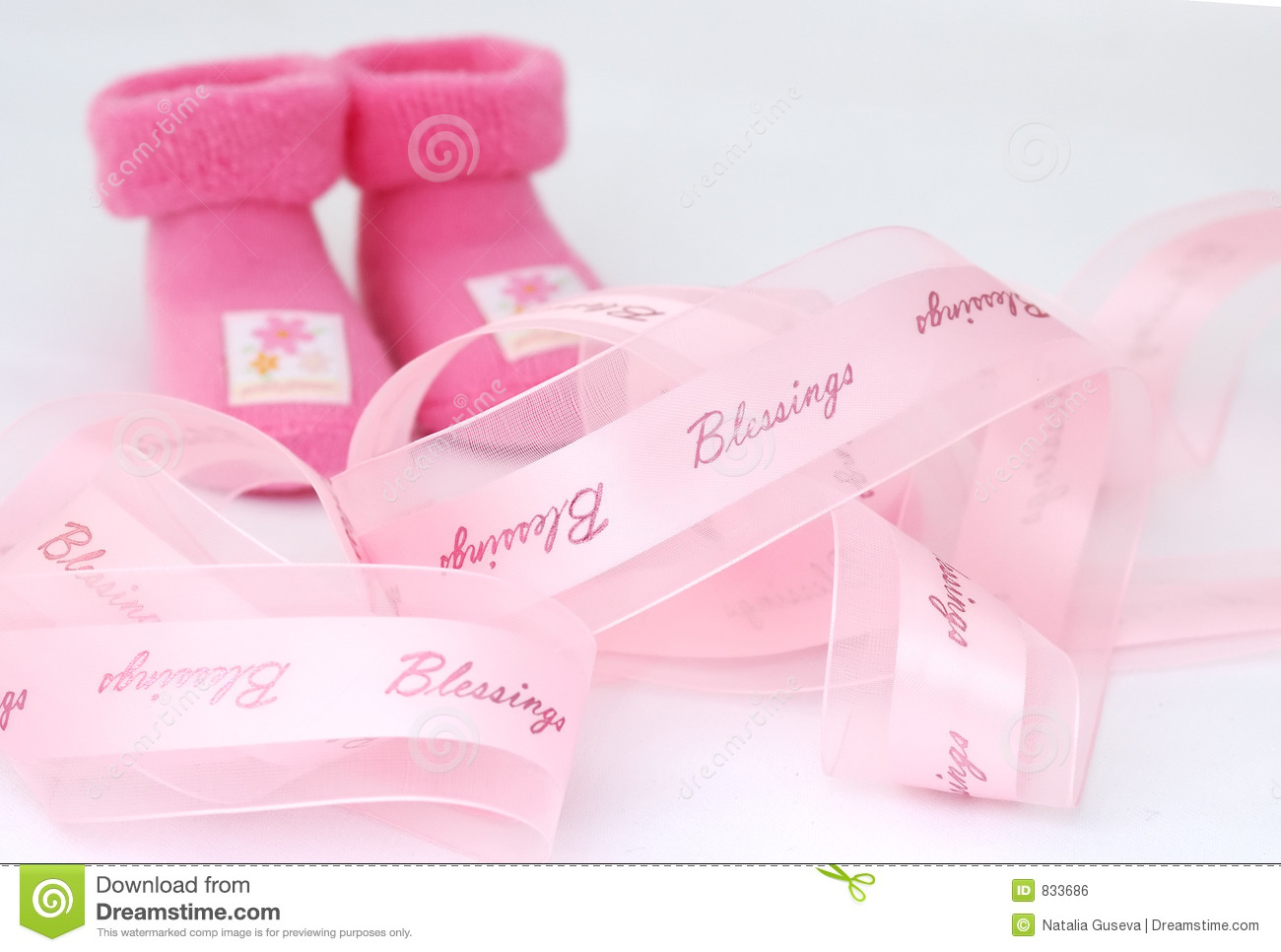 Pink Ribbon With Blessings Print And Two Pink Socks At The Background