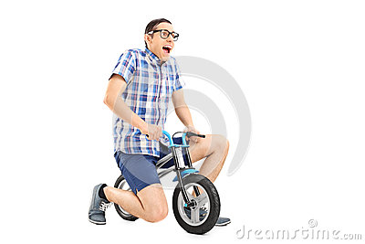 Studio Shot Of A Silly Young Guy Riding A Tiny Bicycle Isolated On