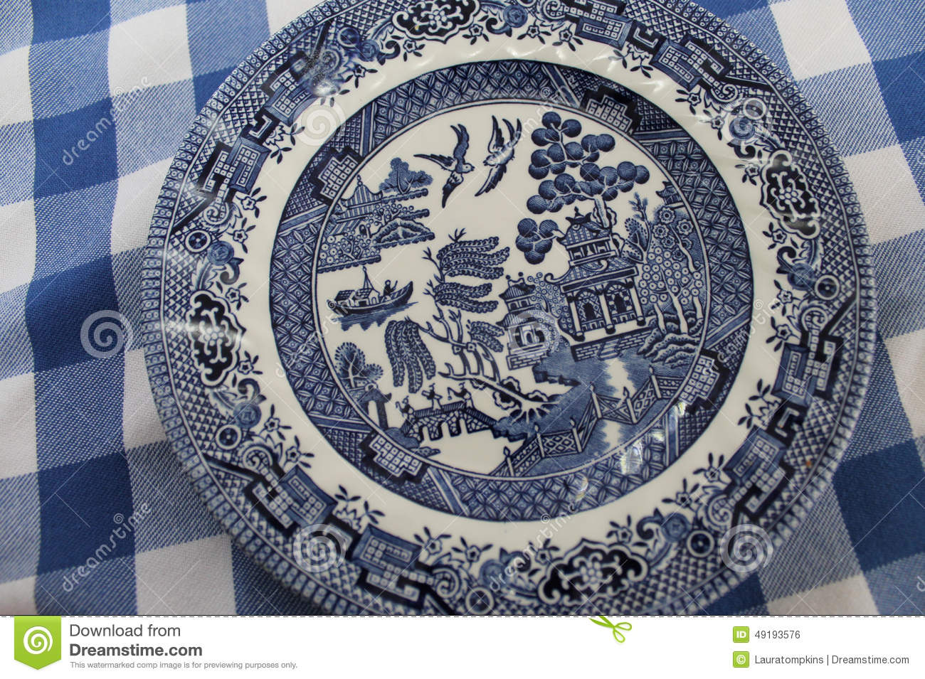 Classic Old Blue Willow China Plate On A Blue And White Tablecloth