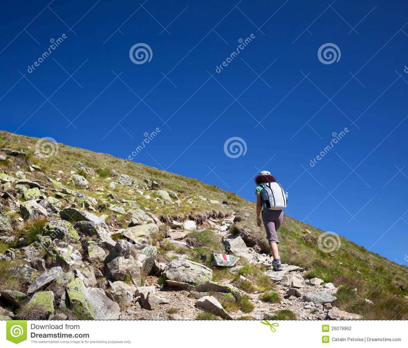 Young Woman With Backpack Hiking Into The Mountains