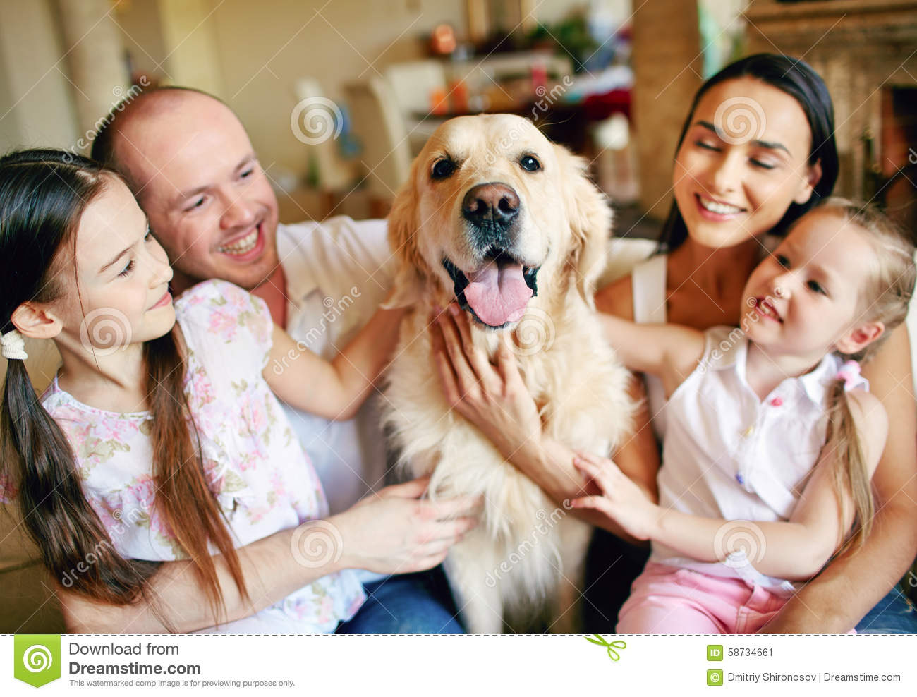Young Friendly Family Of Four Cuddling Their Pet