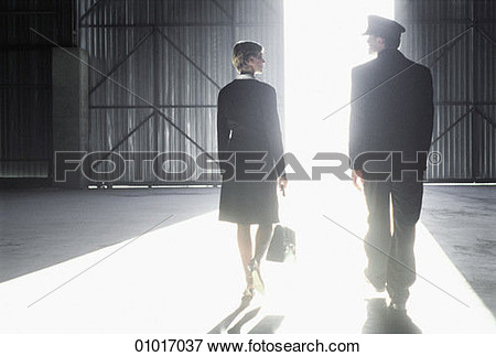 Man And A Woman Walking Out Of A Hanger Into Bright Sunlight View