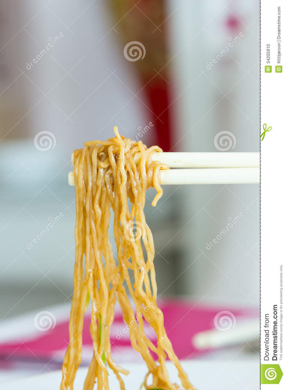 Yellow Noodles With Chopstick Holding Stock Photo   Image  34205910
