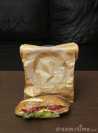 Sandwich In Cellophane Wrap Next To Brown Paper Bag